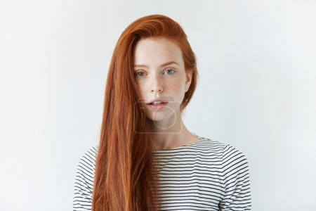 Photo for Pretty student girl with perfect healthy freckled skin looking at the camera with serious expression. Redhead model with green eyes wearing striped top standing against white studio wall background - Royalty Free Image