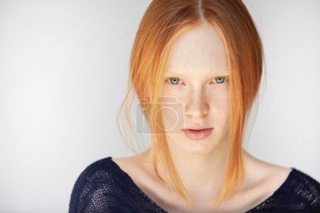 Photo for Close up portrait of happy beautiful redhead girl with perfect healthy skin wearing casual clothes, looking and smiling at the camera with penetrating blue eyes. Human face expressions and emotions - Royalty Free Image