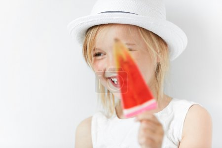 Smiling child hiding behind popsicle