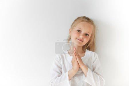 Blond kid folding hands like prayer