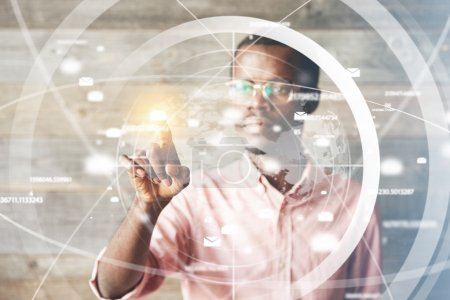 Portrait of African man in glasses, using digital device, pointing at icons on futuristic screen interface against high-tech interior, looking with serious concentrated expression. Selective focus