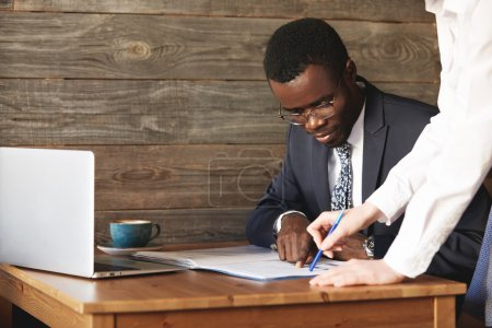 Focused African American businessman checking papers with his personal assistant in white shirt. Young female colleague points at lines in documents, explaining details in a business contract.