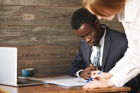 Young redhead Caucasian corporate female worker in white shirt, holding a pen, pointing at a report, explaining business plans for her African partner, working together on a project at a coffee shop