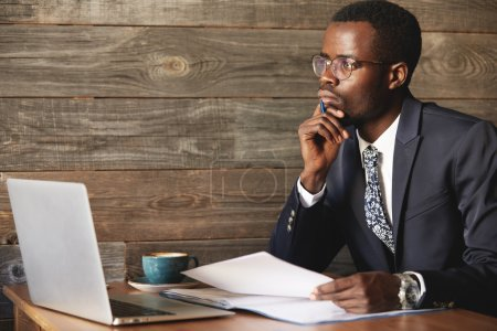 Handsome young African man wearing formal suit sitting at a coffee shop with pensive look, thinking of business plans, holding a pen, leaning his elbow on the table, signing papers, working on laptop