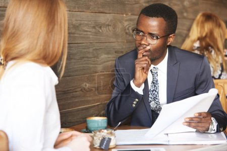 Recruiting and human resource concept. African HR director in suit conducting an interview, looking at female Caucasian candidate with pensive concentrated expression, holding finger on his chin