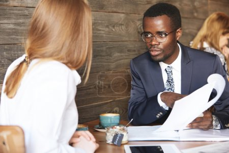 African boss conducting an interview with redhead Caucasian woman, holding job application and listening attentively to candidate. Two office workers discussing a project during lunch break at a cafe