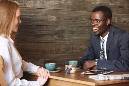 Two business partners sitting in cafe and discussing common project. African American entrepreneur and young Caucasian businesswoman smiling and talking during meeting in a stylish coffee shop.