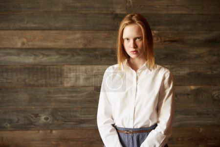 Portrait of a beautiful Caucasian woman looking seriously at camera. Blond girl well-dressed in white shirt, showing neutral emotions as if waiting for somebody to speak. Stylish office look.