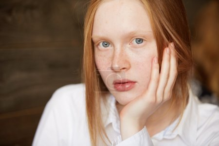Close up portrait of Caucasian blue-eyed girl with blond long hair looking at camera. Young female resting her head on the palm with simple and natural look, innocent appearance and neutral emotions.