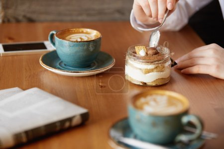 Close up shot of woman's hands eating sweet dessert with a spoon. Young female office worker having coffee with a colleague during lunch break while sitting at the wooden table at a restaurant. Film e