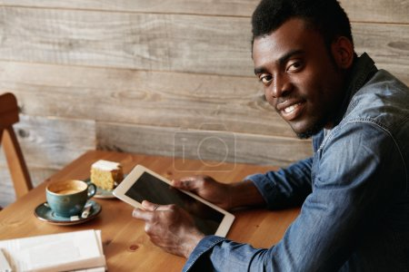 Portrait of handsome black student in denim wear, looking at the camera with happy expression while enjoying leisure time at a coffee shop, using electronic device after classes at university