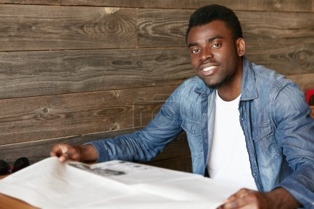 Attractive young African office worker in denim jacket reading tabloid while sitting at the wooden table at a restaurant during lunch break. Handsome black student relaxing at a student cafe