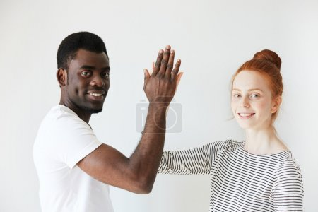 Portrait of a young couple making high five and smiling at camera in white studio. Mix of African American appearance with Caucasian one makes photo looks contrasting. Common victory and partnership.