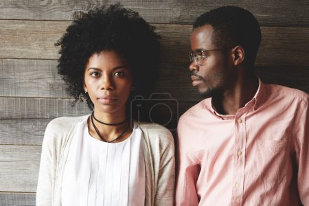 Serious African student looking at girlfriend