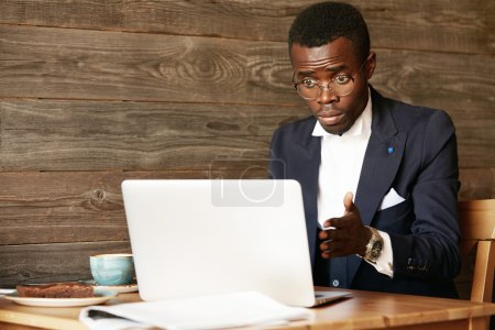 Shocked African businessman looking at laptop