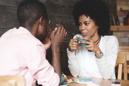 Black girl with Afro hairstyle holding a cup of coffee, listening and looking at her boyfriend with amorous expression. Loving couple enjoying time together at a restaurant on Saint Valentine's Day