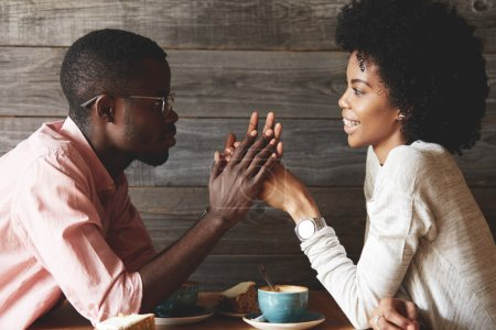Loving African couple enjoying time together sitting at a coffee shop, holding hands, looking at each other and smiling with amorous expression, feeling pure and tender love, against wooden wall
