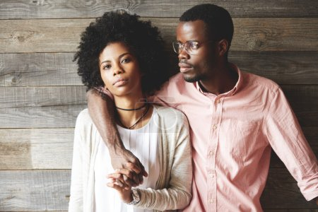 Young unhappy African couple: man in glasses hugging his girlfriend, looking into the distance, pretty woman looking at the camera, holding boyfriend's hand, isolated on a background of wooden wall