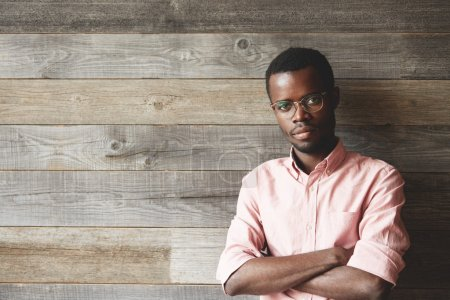 Handsome dark-skinned young man wearing glasses and pink shirt, looking at the camera with serious confident expression, standing against wooden wall with copy space for your promotional content