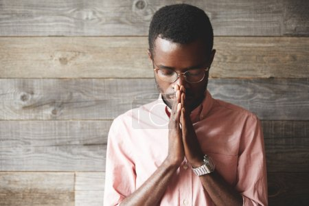 Young meditating and praying African American man wearing pink shirt and glasses, holding hands in prayer against his lips, hoping for the best, asking for wisdom and strenght, with closed eyes