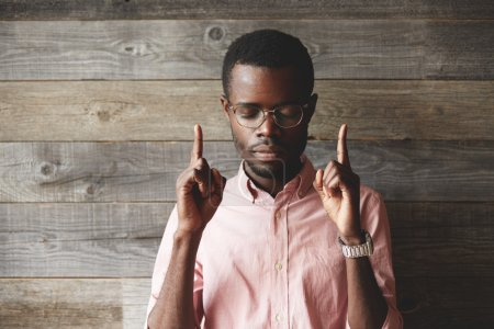 Portrait of handsome young African man, standing against wooden wall background, with closed eyes, showing index fingers up, trying to remember something very important, looking concentrated