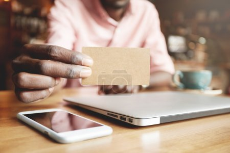 African in pink shirt holding a blank business card with copy space for your promotional content, surrounded with generic laptop and cell phone with blank screen. Selective focus on the visiting card