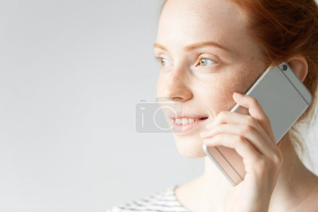 Technology and communication concept. Highly-detailed portrait of teenage girl with red hair and freckles speaking on mobile phone, looking away, smiling while ordering pizza via food delivery service