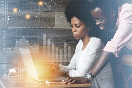 Happy African freelancer watching his female partner with Afro haircut showing graphics, demonstrating growth rates in sales, pointing a finger at the laptop screen. Double exposure. Visual effects