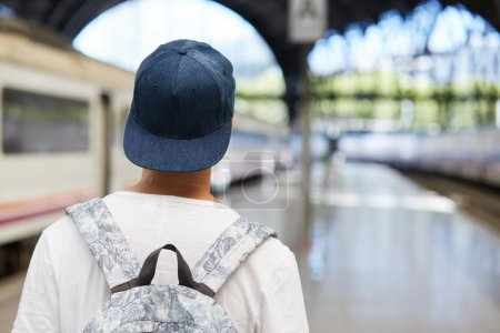 teenager boy in cap and with backpack