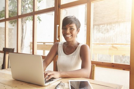 Young smiling dark-skinned female with short haircut sitting at the wooden table in front of notebook, browsing online-shops, dressed casually, looking at the camera with happy face expression