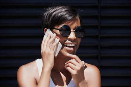 Outdoor portrait of fashionable African American woman in round shades talking on smart phone to her friend, discussing latest news, smiling, laughing, looking cheerful and excited, touching her chin