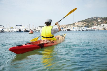 man kayaking on canoe