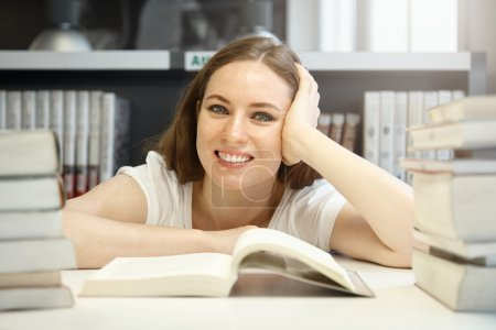 student studying with textbook at library