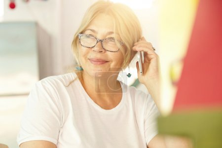grandmother with spectacles speaking on smart phone
