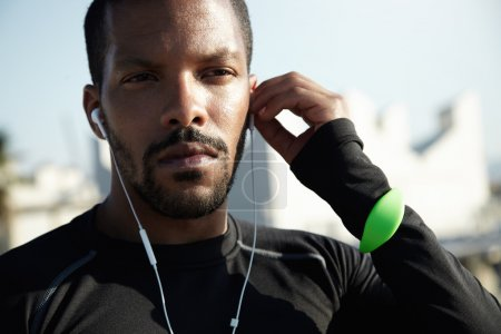Photo for Close up shot of serious and confident black sportsman in black training outfit looking into distance with deep-in-thoughts expression, listening to audio book with his earphones, touching his head - Royalty Free Image