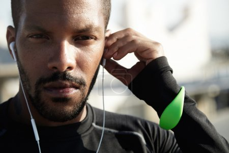 Athlete putting headphones in ears