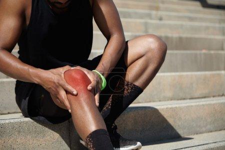 African athlete clutching his injured knee