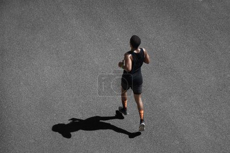 African runner training on black pavement