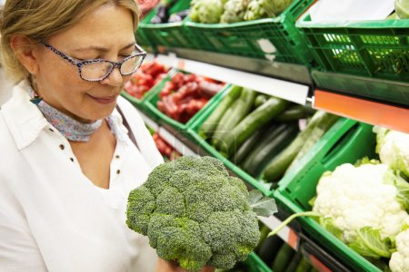 middle-aged woman holding fresh  broccoli