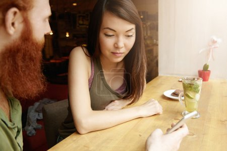 Interracial couple having fresh drinks at coffee shop. Caucasian bearded man talking on his start up project, holding cell phone, showing pictures to his Asian friend who is looking at screen
