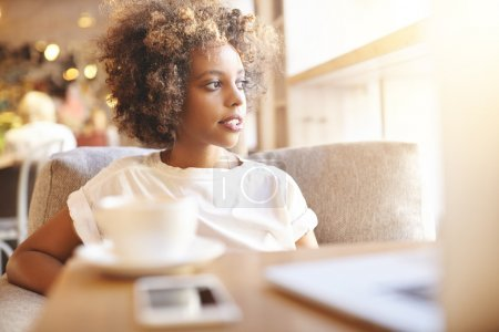 Photo for Selective focus. Headshot of serious black woman with Afro hairstyle, dressed in casual white top, sitting on sofa at cafe and waiting for her friend. African student using laptop and having coffee - Royalty Free Image