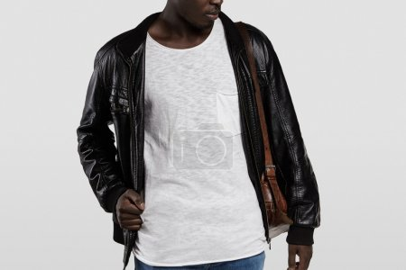 Indoor portrait of attractive young African male model dressed casually, posing in studio. Stylish dark-skinned student wearing leather jacket and shoulder bag, getting ready for university