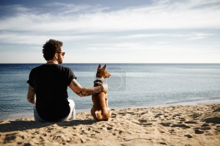 Caucasian man in sunglasses sitting in beach with friends dog