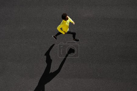 Top view athlete runner training at black road in yellow sportsw