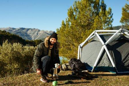 Adventure hiking man drinking coffee near tent. Smiling happy ma