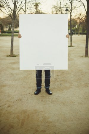 Man holding white blank poster on a street