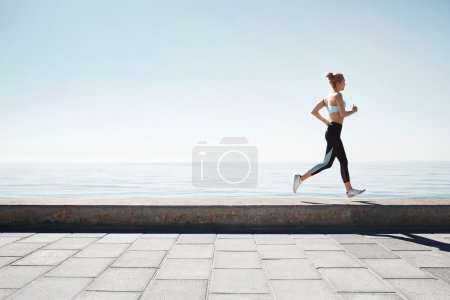 Photo for Running asian woman. Female runner training outdoors seaside athlete on beautiful sunset or morning at beach. - Royalty Free Image