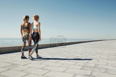 Photo for Couple female running exercising jogging happy on waterfront training as part of healthy lifestyle. Two back young fit girls runners. - Royalty Free Image