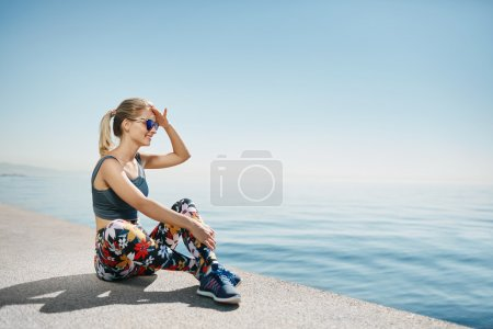 Fitness blonde woman runner relaxing after city running and work