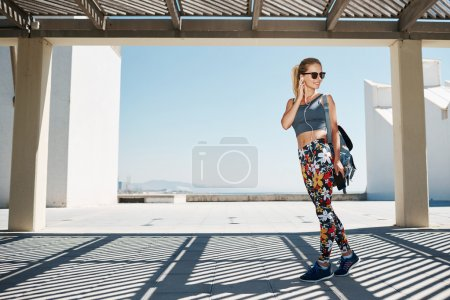Young fitness blonde woman in sportswear listening music with he